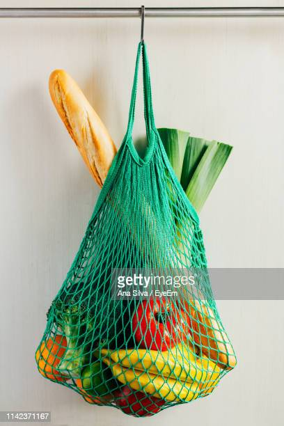 food in net hanging against wall - 網状 ストックフォトと画像