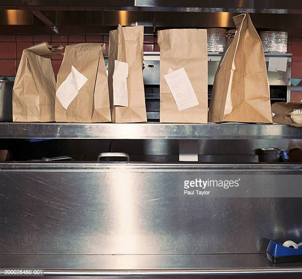 food in take out bags with receipts, sitting on restaurant shelf - take out food stock pictures, royalty-free photos & images