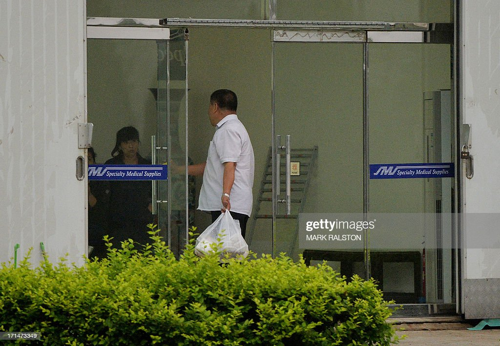 Food is delivered to the compound where US businessman Chip Starnes has been held hostage for five days over a wage dispute at his Specialty Medical Supplies factory in Huairou, Beijing on June 25, 2013. Starnes, who had come from the US-based company to lay off 30 employees, said the remaining 100 then barred him from leaving until they reached a resolution. AFP PHOTO/Mark RALSTON