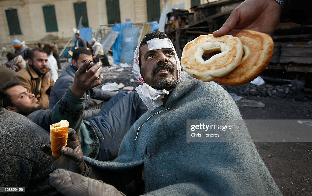 Food is offered to a wounded anti-government protester who spent the night manning makeshift barriers protecting the anti-government movement in Tahrir Square the morning of February 6, 2011 in Cairo, Egypt. An uneasy stand-off remains between anti and pro-government factions in Egypt's central square as the protests continue unabated.