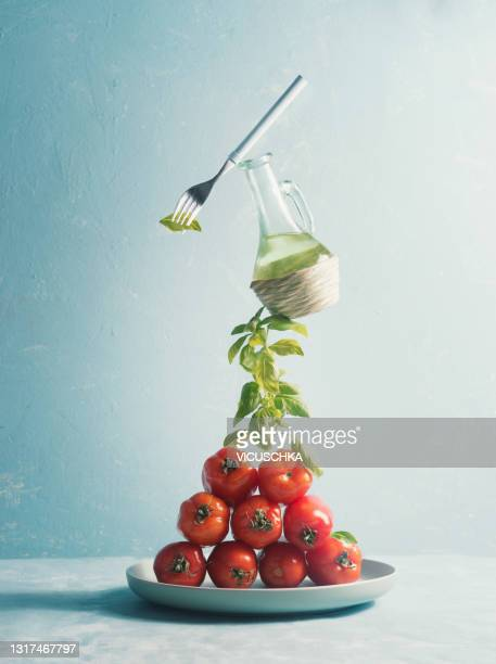 food levitation with heap of tomatoes on plate with balanced basil bunch, olive oil and fork at  blue background. creative food - fork stock pictures, royalty-free photos & images