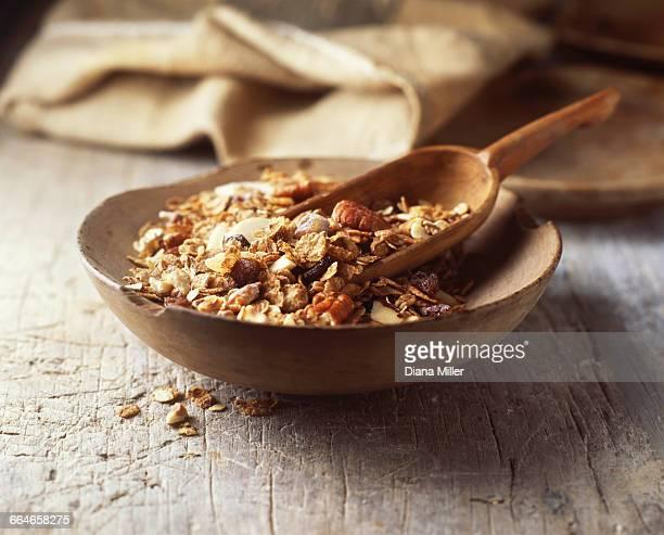 Food, muesli in wooden bowl, pecans, rolled oats, dried fruit, raisins, nuts, vintage