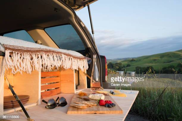Food on cutting board at car trunk of sports utility vehicle by rolling landscape