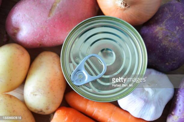 food packaging tin can soup surrounded with fresh raw root vegetables - rafael ben ari fotografías e imágenes de stock