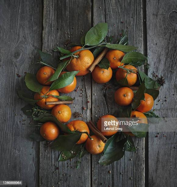 food photography of christmas wreath of bright citrus fruits oranges, tangerines with green leaves and spice on a dark wooden textured boards background close up, top view - season stock pictures, royalty-free photos & images