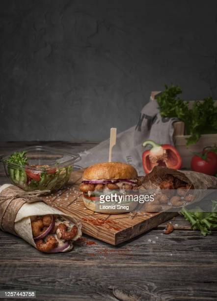 food photography of still life with fast food burger, salad, shrimp and roll side view on a wooden board in a rustic style - hamburger stock pictures, royalty-free photos & images