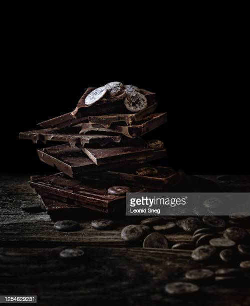food photography of tower of broken dark chocolate close up front view on a dark wooden background - dark chocolate stock pictures, royalty-free photos & images