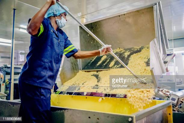 Food Processing Plant Worker Shoveling Dough