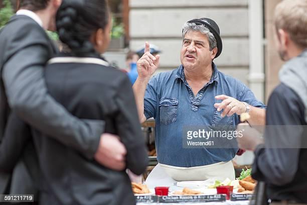 Food seller at city market talking to customers