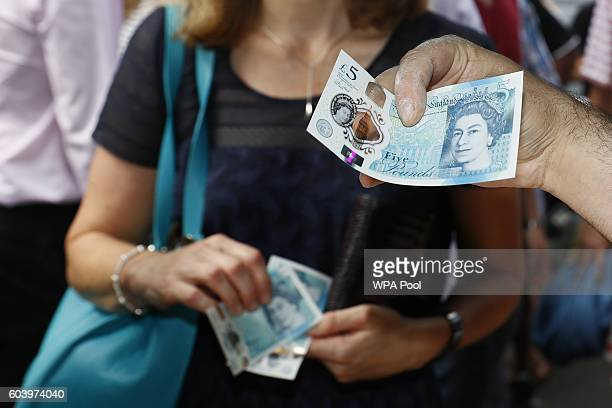 A food seller holds a new polymer five pound note at Whitecross Street Market on September 13 2016 in London United Kingdom The new plastic note is...