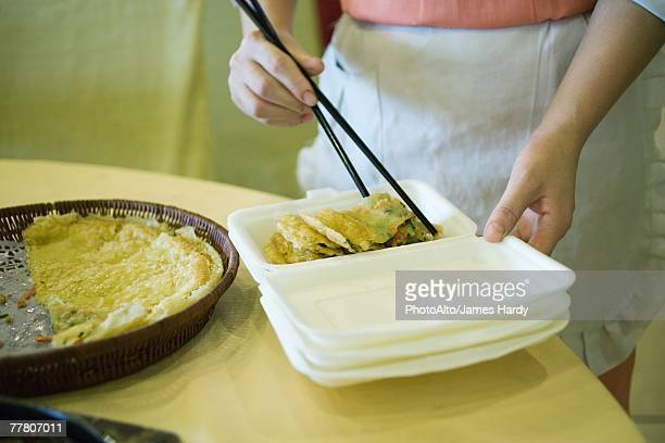 Food service personnel using chopsticks to place food in polystyrene container
