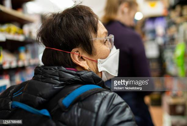 Food shopper wearing a surgical mask stands in the checkout line at Key Foods market in Brooklyn, New York on March 20, 2020. The coronavirus...