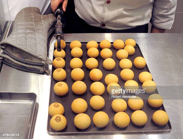 A food shop's logo is burned onto the tops of a tray of mangu a popular traditional Japanese confection Most have an outside made from flour and rice...