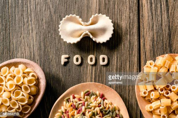 Food sign of Italian pasta on rustic wooden table. Colored pasta in a wooden spoons.
