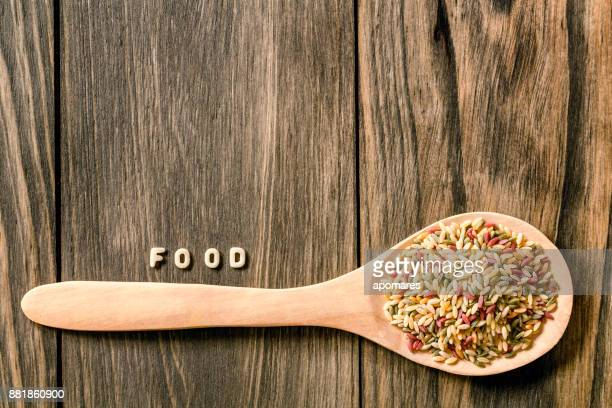 Food sign of Italian pasta over rustic wooden table. Copy space on board. Colored Orzo pasta in a wooden spoon.