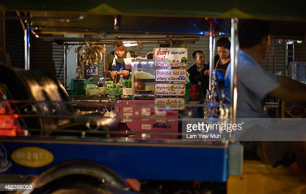 """Food stall photographically """"framed"""" by a passing Tuk Tuk in the street of Bangkok."""