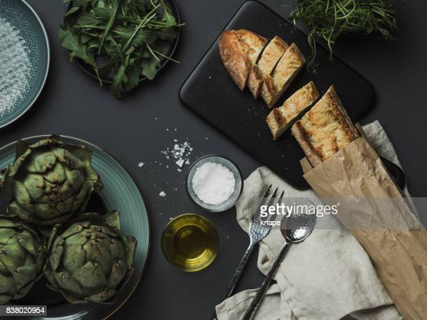 food table setting with artichoke bread oils and salt - kitchen utensil stock pictures, royalty-free photos & images