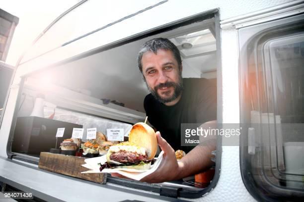 food truck eigenaar portie hamburger - food truck stockfoto's en -beelden