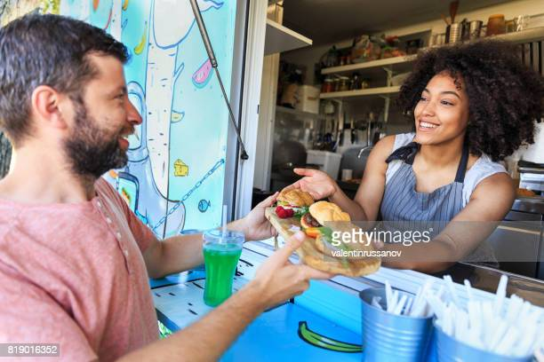 food truck owner serving sandwiches to customer - food truck stock photos and pictures