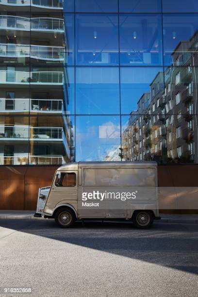 food truck parked on city street against modern glass building - food truck fotografías e imágenes de stock