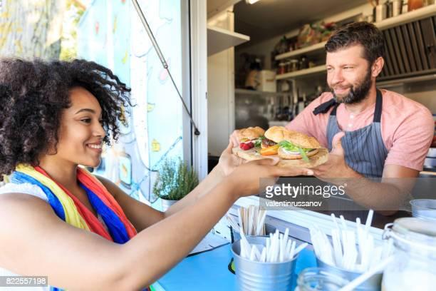 顧客にサンドイッチを提供食品トラック労働者