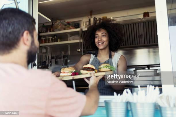 Food van worker giving order to customer