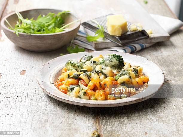 food, vegetarian meals, vegetable pasta bake, melted cheese, onions, peas, broccoli, rocket in bowl, cheese and cheese grater, vintage bowl, rustic wooden table - piatto stoviglie foto e immagini stock