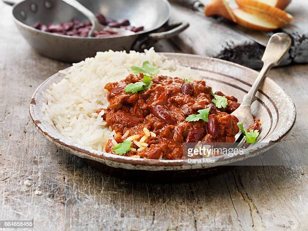 Food, vegetarian meals, vegetarian chilli and rice, kidney beans, tomatoes, fresh coriander, onions, vintage bowl, rustic wooden table