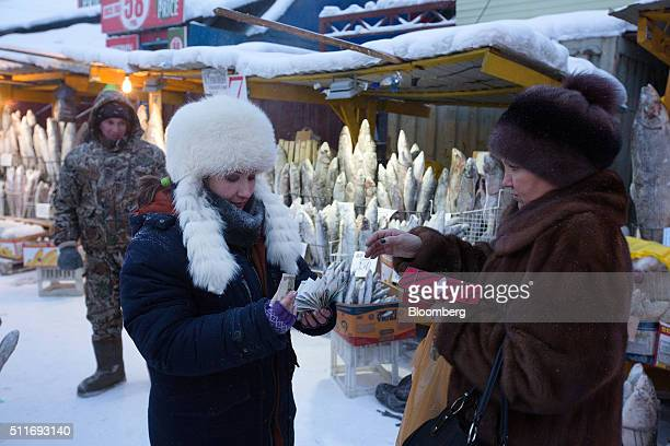 A food vendor left hands over Russian ruble banknotes to a customer in the Krestyansky open air market in Yakutsk Sakha Republic Russia on Wednesday...
