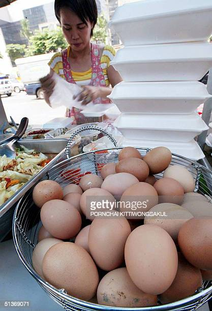 A food vendor prepares lunch boxes next to basket with eggs at a streetside in Bangkok 29 September 2004 during a second bird flu wave of the disease...