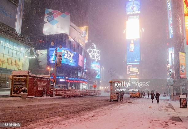 CONTENT] A food vendor rolls his food cart along the empty snowcovered street in Times Square during a winter storm in midtown Manhattan