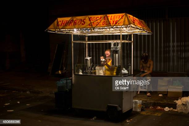 A food vendor selling churros cleans the apparatus on her stall in Praca Sao Sebastiao in central Manaus on June 15 2014 in Manaus Brazil England...