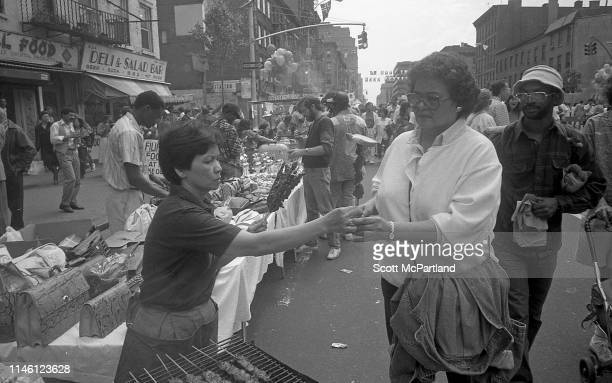 A food vendor serves a kebab to a customer on 9th Avenue in Hell's Kitchen during the International Food Festival New York New York May 14 1988