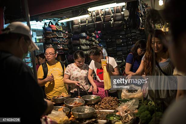 A food vendor serves customers at a street market in Taipei Taiwan on Saturday May 16 2015 Taiwan is scheduled to release gross domestic product...