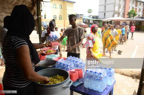A food vendor serving food as people queue in line to collect food as Lagos state government begins distribution of meals to Youths in verious LCDAs...