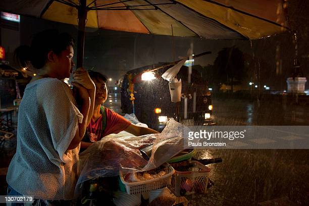 Food vendors fight a rainstorm near the Chayo Praya river as rising waters threaten parts of the capitol city October 28 2011 in Bangkok Thailand...