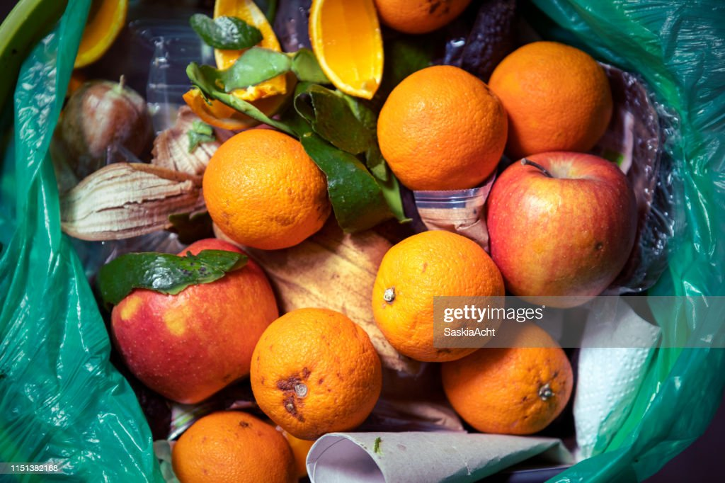 Food waste problem, leftovers Thrown into into the trash can. Spoiled food in refuse bin. Spoiled oranges and apples close up. Ecological issues. Garbage. Concept of food waste reduction. From above. : Stock Photo