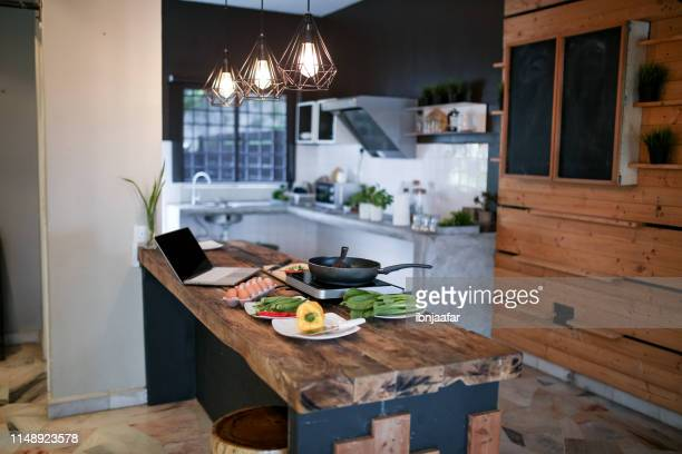 food with pan and laptop at kitchen - ibnjaafar stock photos and pictures