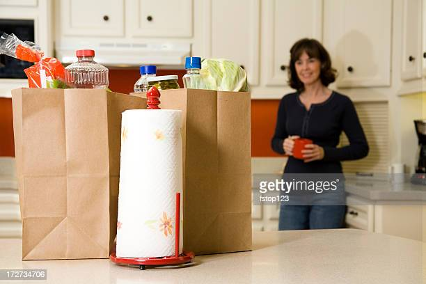 Food:  Woman looking at Grocery bags in the kitchen