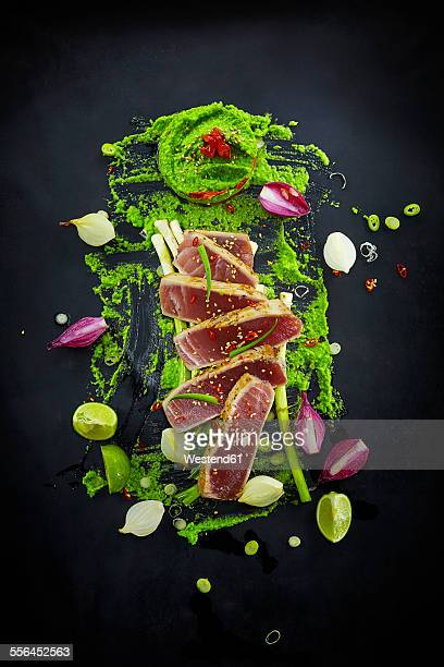 Foodart, slices of raw tuna with herbs and wasabi pea paste