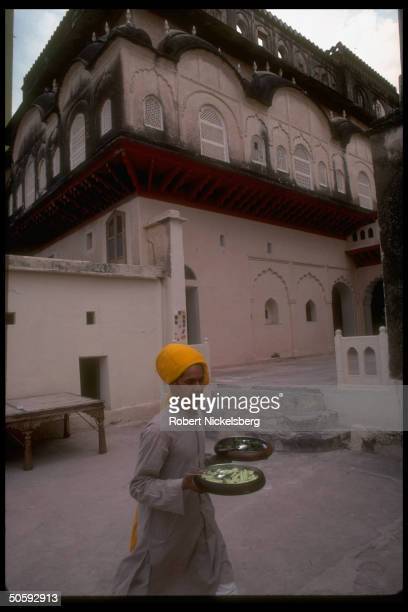 Foodbearing youth in courtyard at Neemrana Fort built in 1464 on DelhiJaipur highway in Rajput palaces temples fortressesgraced Rajasthan India