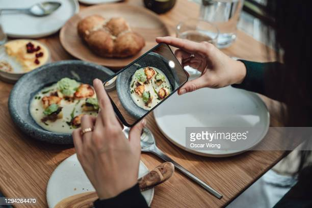 foodie photographing food at restaurant and share on social media - rear view stock pictures, royalty-free photos & images