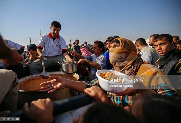 Foods are distributed to Iraqi people at Khazir refugee camp after they had fled from clashes between Iraqi army forces and Daesh terrorists at...