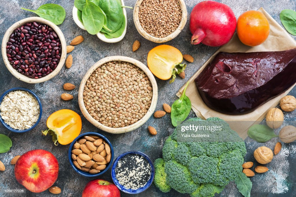 Foods high in iron. liver, broccoli, persimmon, apples, nuts, legumes, spinach, pomegranate. Top view, flat lay. : Stock Photo