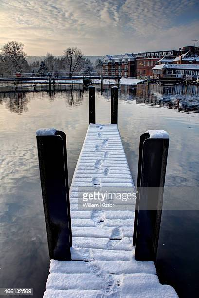 Foosteps in fresh snow disappearing off the end of the dock. Marlow, Buckinghamshire, England.