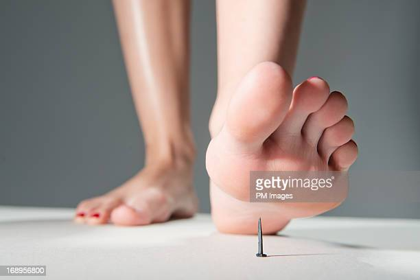 foot about to step on nail - female feet soles stock photos and pictures