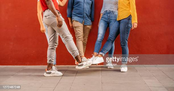 foot bump greeting - red pants stock pictures, royalty-free photos & images