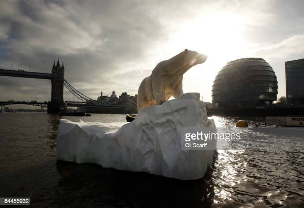 Foot high sculpture of a polar bear, afloat on a small iceberg on the River Thames, passes in front of Tower Bridge and City Hall on January 26, 2009...
