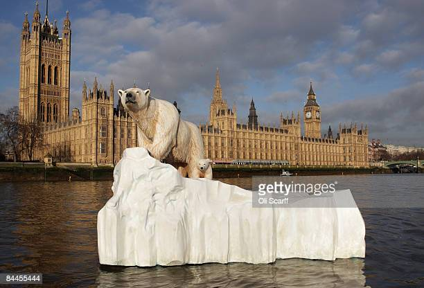 Foot high sculpture of a polar bear and cub, afloat on a small iceberg, passes in front of the Houses of Parliament on the River Thames on January...