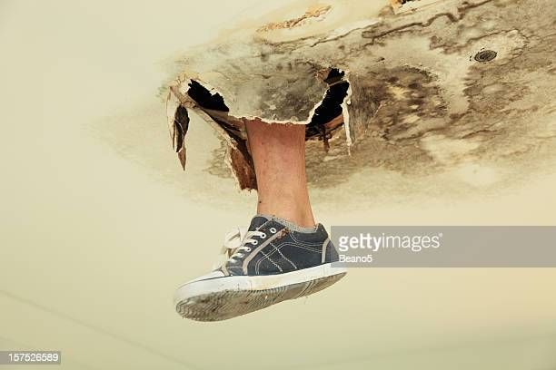 Foot in canvas shoe poking through rot in the ceiling